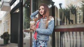 Jovem mulher que está com café, na frente das janelas espelhadas outdoor filme
