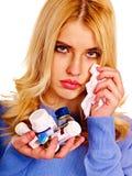 A jovem mulher que está com a gripe toma comprimidos. Fotos de Stock