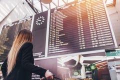 Jovem mulher que está contra o placar do voo no aeroporto foto de stock royalty free
