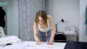 Jovem mulher que está de dobra sobre a tabela em costurar o estúdio e em esboçar os vestidos futuros Criação do desenhista nova video estoque
