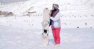Jovem mulher que está de espera com seu snowboard Fotografia de Stock Royalty Free