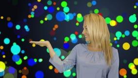 Jovem mulher que está de sorriso guardando sua mão que mostra algo na palma aberta, conceito do produto da propaganda video estoque