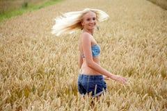 Jovem mulher que está em um campo de milho Fotografia de Stock Royalty Free