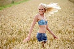 Jovem mulher que está em um campo de milho Imagens de Stock Royalty Free