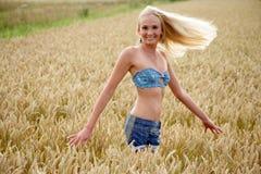 Jovem mulher que está em um campo de milho Imagem de Stock