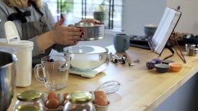 Jovem mulher que está na cozinha e que peneira a farinha na bacia Fêmea loura que pesa os ingredientes para cozinhar filme