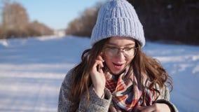Jovem mulher que está na estrada do inverno, está falando no telefone no dia ensolarado filme