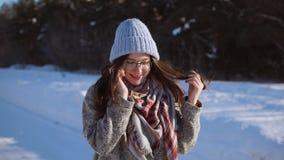 Jovem mulher que está na estrada do inverno, está falando no telefone no dia ensolarado video estoque