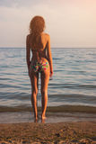 Jovem mulher que está no litoral Imagens de Stock Royalty Free