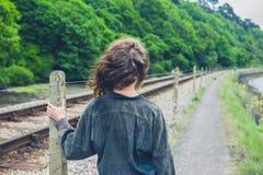 Jovem mulher que está pela trilha de estrada de ferro Imagem de Stock Royalty Free