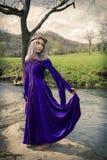 Jovem mulher que está pelo rio em um vestido roxo Fotografia de Stock Royalty Free