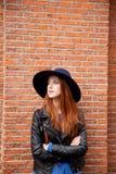 jovem mulher que está perto da parede da construção de tijolos Foto de Stock