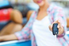 Jovem mulher que está perto de um convertible com chaves à disposição Fotografia de Stock