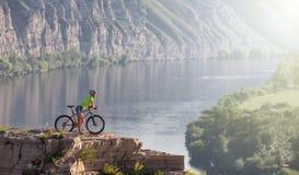 Jovem mulher que está na montanha com a bicicleta acima do rio Fotos de Stock