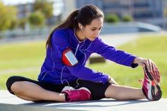 Jovem mulher que estica e que prepara-se para correr Foto de Stock Royalty Free