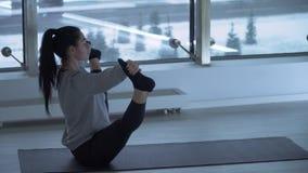 Jovem mulher que estica os pés que fazem a ioga que senta-se na esteira no gym com as grandes janelas do chão ao teto Arquitectur vídeos de arquivo