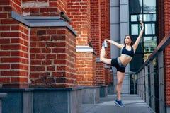 A jovem mulher que estica para fora seu pé que faz a ioga exercita fora Fotografia de Stock