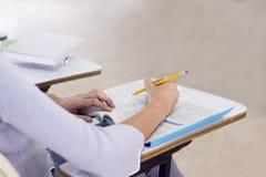 Jovem mulher que estuda para um teste, mãos do estudante que escrevem no livro na sala de aula Aprendizagem e educação, conceito  foto de stock royalty free