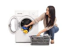Jovem mulher que esvazia uma máquina de lavar fotografia de stock royalty free