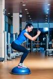 Jovem mulher que executa exercícios da ginástica aeróbica da etapa dentro Fotografia de Stock Royalty Free