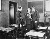 Jovem mulher que executa para dois homens em uma sala de classe (todas as pessoas descritas não são umas vivas mais longo e nenhu Foto de Stock Royalty Free