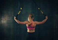 Jovem mulher que exercita com as correias da aptidão do trx imagens de stock royalty free
