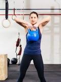 Jovem mulher que exercita com kettlebell Fotografia de Stock