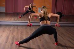 Jovem mulher que exercita com pesos da mão no estúdio Fotografia de Stock Royalty Free