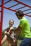 Jovem mulher que exercita com um instrutor pessoal fora em ensolarado Imagem de Stock Royalty Free
