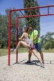 Jovem mulher que exercita com um instrutor pessoal fora em ensolarado Fotografia de Stock