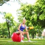 Jovem mulher que exercita com um peso e uma bola dos pilates em uma paridade Fotos de Stock Royalty Free