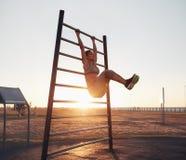 Jovem mulher que exercita em barras de parede com seus pés acima fotos de stock royalty free