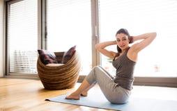 Jovem mulher que exercita em casa, fazendo triturações foto de stock royalty free