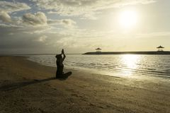 Jovem mulher que exercita a ioga na praia de Sanur Imagem de Stock Royalty Free