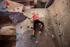 Jovem mulher que exercita no gym de escalada interno Foto de Stock