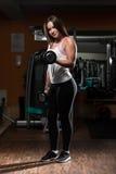 Jovem mulher que exercita o bíceps com pesos Imagem de Stock