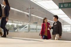 Jovem mulher que fala ao homem na plataforma railway, China Imagens de Stock