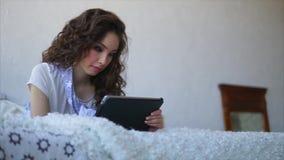 Jovem mulher que fala com os amigos que usam a tabuleta ao encontrar-se na cama no quarto filme