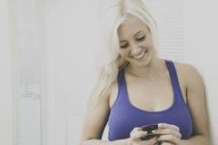 Jovem mulher que fala em um smartphone Fotografia de Stock Royalty Free