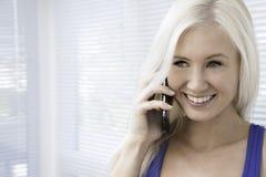 Jovem mulher que fala em um smartphone Fotografia de Stock