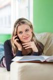 Jovem mulher que fala em um telefone móvel ao encontrar-se em casa no Imagens de Stock Royalty Free