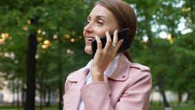 Jovem mulher que fala no phonne móvel no parque video estoque