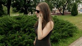 Jovem mulher que fala no Smart-telefone ao andar fora Tiro constante da came vídeos de arquivo