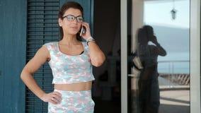 Jovem mulher que fala no smartphone ao estar no balcão na sala de visitas filme