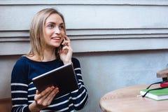 Jovem mulher que fala no smartphone e no sorriso A moça com tabuleta e sellphone e aprende ao descansar na Fotos de Stock