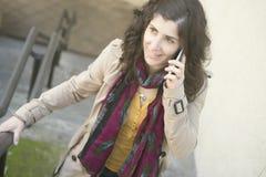 Jovem mulher que fala no telefone ao andar acima em escadas fotografia de stock royalty free