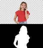Jovem mulher que fala no telefone celular ao andar, Alpha Channel imagem de stock