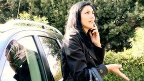 Jovem mulher que fala no telefone celular na frente de seu carro filme