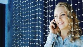 Jovem mulher que fala no telefone no clube Estar sobre a decoração dos grânulos de vidro filme