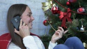 Jovem mulher que fala pelo telefone celular e que sorri perto da árvore de Natal filme